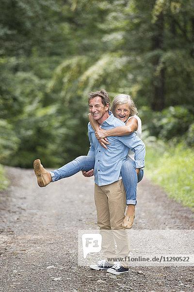 Älterer Mann  der seiner Frau eine Huckepackfahrt auf einem Waldweg anbietet.