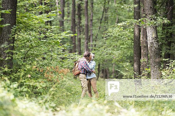 Seniorenpaar beim Küssen im Wald