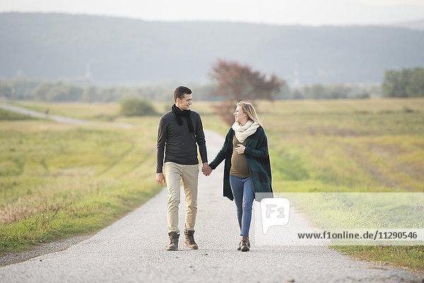 Happy expectant parents walking in rural landscape