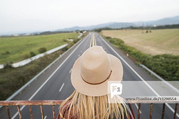 Frau auf der Brücke mit Blick auf die Autobahn