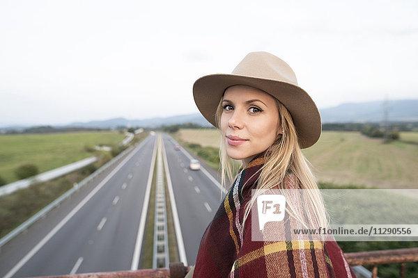 Porträt einer jungen Frau auf der Autobahnbrücke