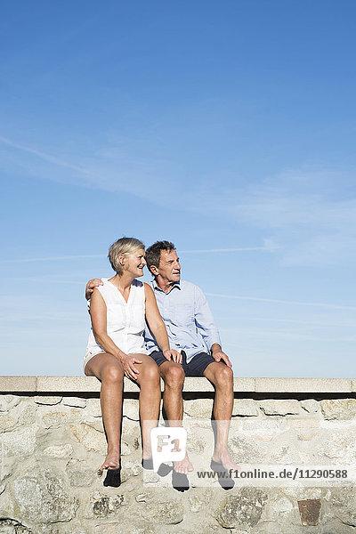 Seniorenpaar sitzt barfuß an einer Wand vor dem Himmel und schaut sich etwas an