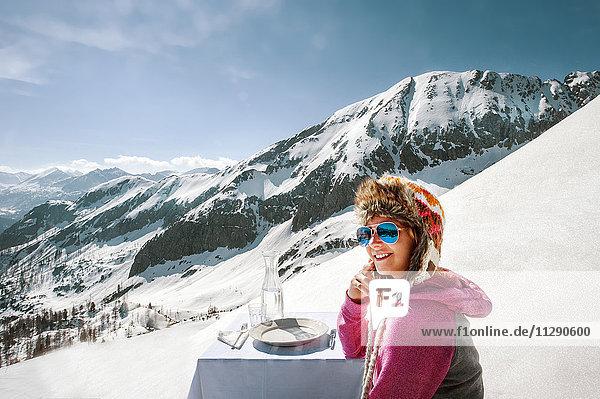 Junge Frau sitzt am gedeckten Tisch in den Bergen