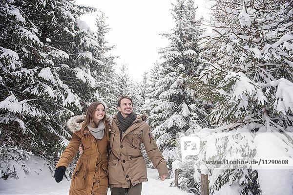 Glückliches Paar beim Wandern im Winterwald
