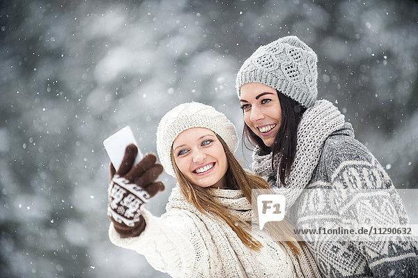 Porträt von zwei Freunden  die im Winter Selfie mit dem Smartphone machen