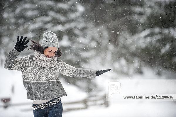 Fröhliche Frau in Strickwaren tanzend im Schnee Fröhliche Frau in Strickwaren tanzend im Schnee