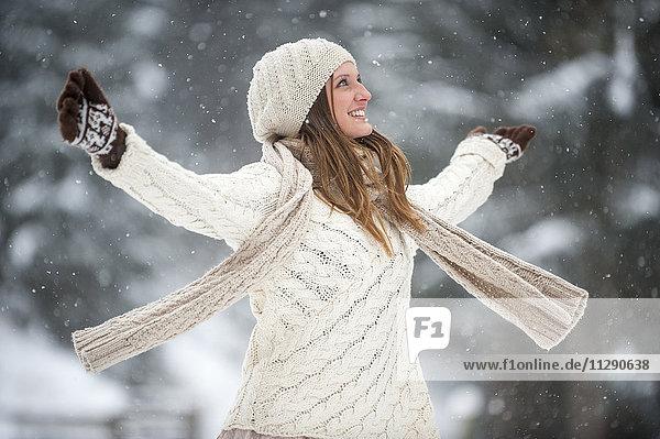 Glückliche blonde Frau in Strickwaren im Winter