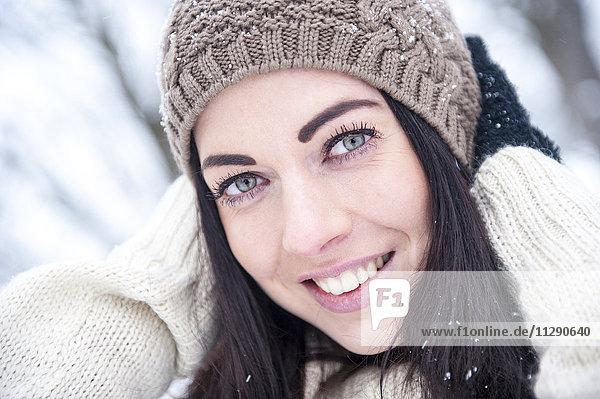 Portrait of smiling woman wearing knitwear in winter