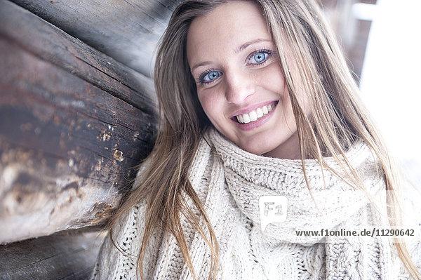 Porträt einer lächelnden blonden Frau in Strickwaren im Winter