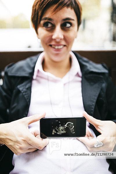 Schwangere Frau mit Ultraschallbild auf dem Handy