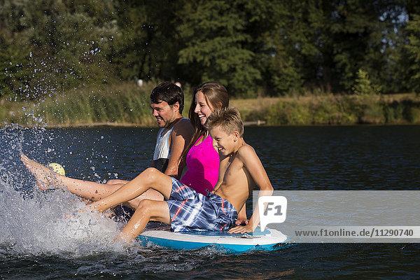Junges Paar und ein Junge sitzen auf dem SUP Board und spritzen mit Wasser.
