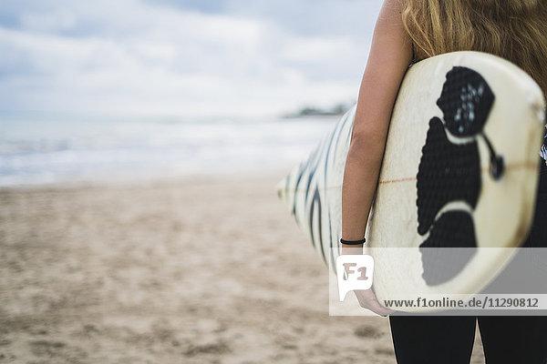 Frau mit Surfbrett am Strand  Teilansicht