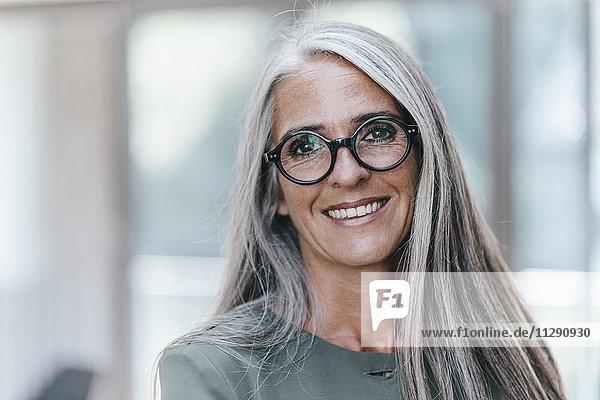 Porträt einer lächelnden Frau mit langen grauen Haaren