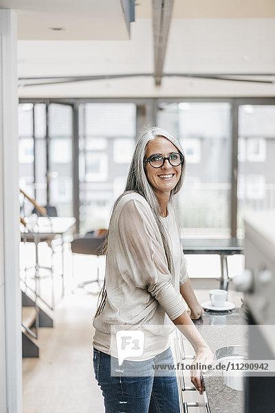 Lächelnde Frau mit langen grauen Haaren in der Küche