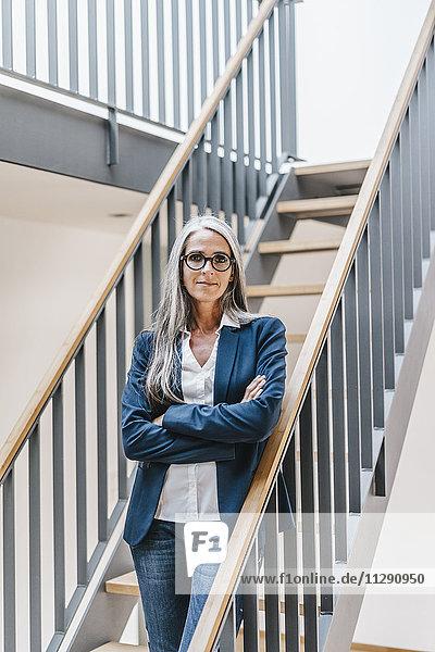 Selbstbewusste Geschäftsfrau mit langen grauen Haaren auf der Treppe stehend