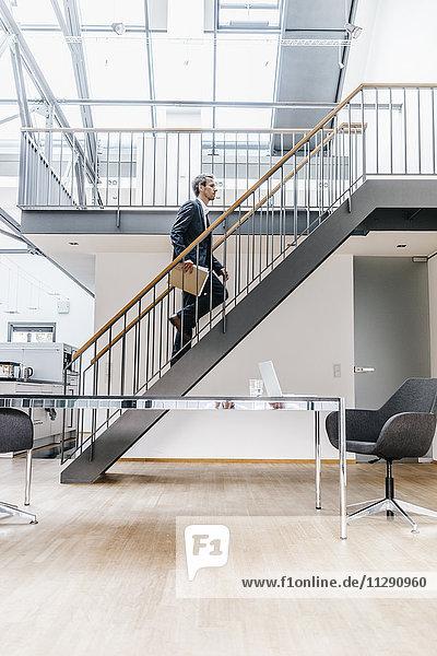 Geschäftsmann  der auf einer Treppe in einem Loft läuft.