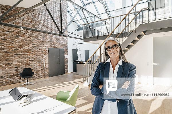 Lächelnde Geschäftsfrau mit langen grauen Haaren steht im modernen Büro