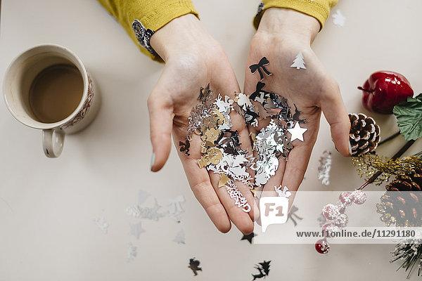 Weihnachtsschmuck auf den Handflächen einer Frau