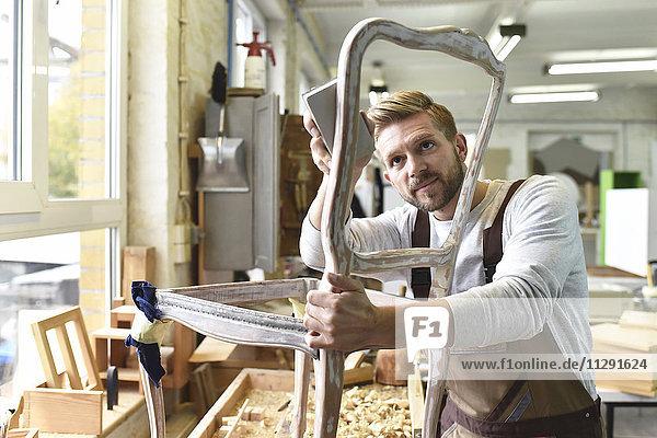 Schreiner beim Restaurieren eines Holzstuhls