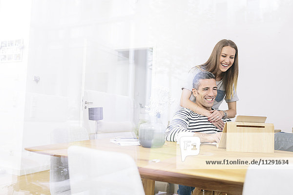 Happy couple at home using tablet