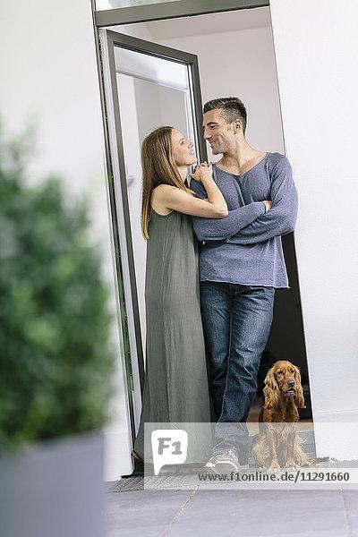 Lächelndes Paar mit Hund an der Terrassentür stehend