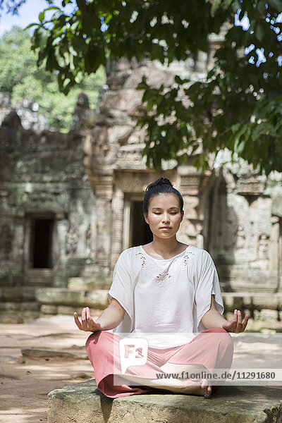 Kambodscha  Angkor  Siem Reap  junge Frau beim Yoga vor dem Ta-Som-Tempel
