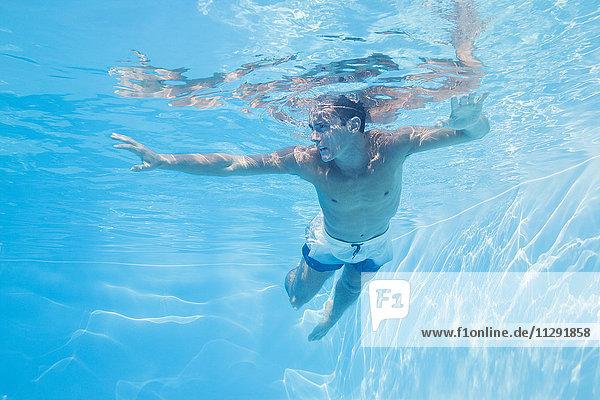 Junger Mann unter Wasser im Pool