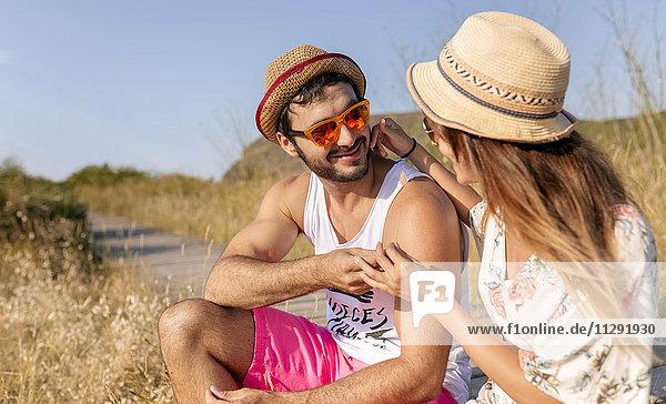 Zärtliches verliebtes Paar mit Strohhut und Sonnenbrille