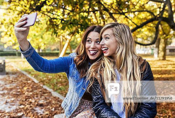 Two playful young women taking a selfie in a park in autumn