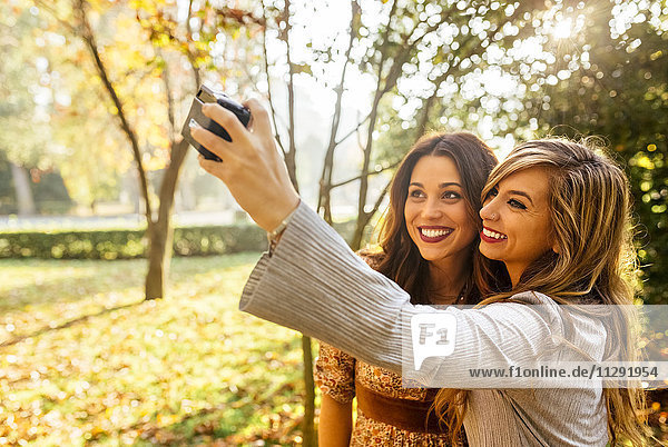 Two smiling young women taking a selfie in a park in autumn