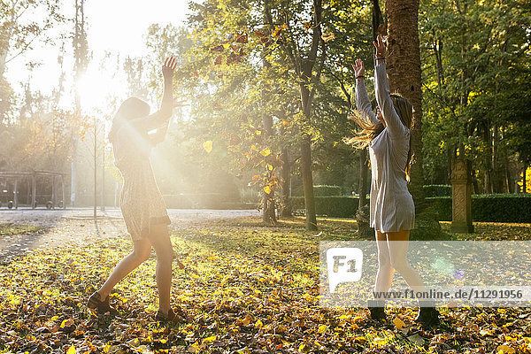 Two playful young women in a park in autumn