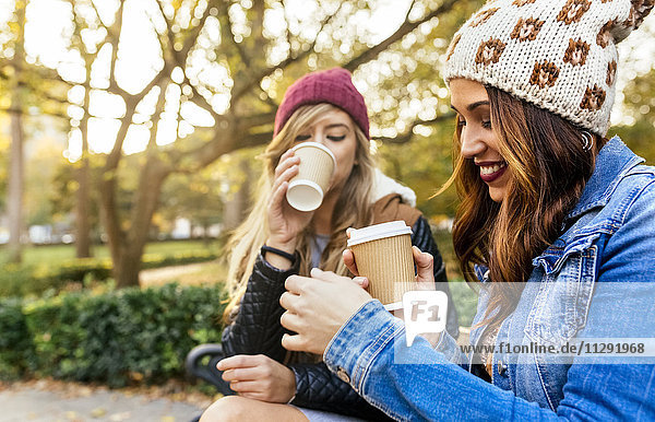 Two young women drinking coffee in a park in autumn