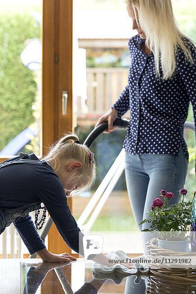 Mädchen putzt den Glastisch  während ihre Mutter Staub saugt.
