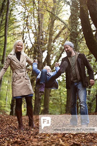 Eltern spielen mit der Tochter im Herbstwald