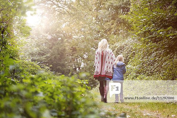 Rückansicht von Mutter und kleiner Tochter beim Spaziergang im Herbstwald