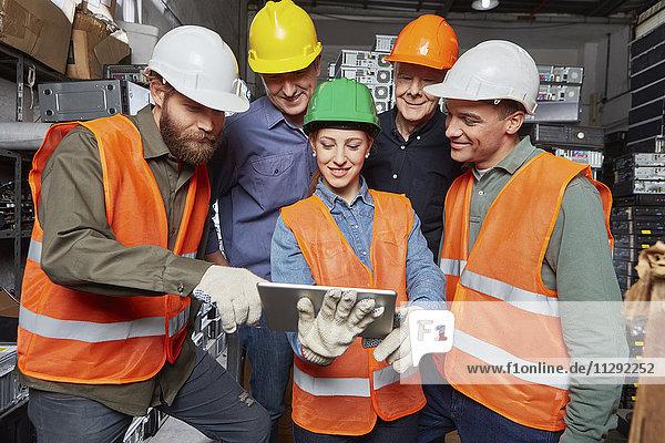 Arbeiter in einer Computer-Recyclinganlage mit digitalen Tabletten