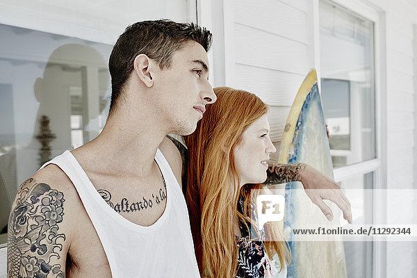 Junges Paar mit Surfbrett steht vor dem Strandhaus und schaut in die Ferne.