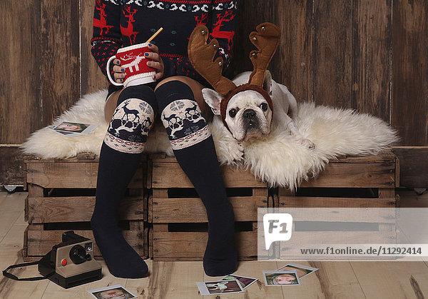 Junge Frau in Wintermode sitzend neben ihrer französischen Bulldogge zur Weihnachtszeit