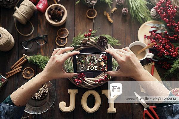 Frauenhände fotografieren selbstgemachten Adventskranz mit Smartphone