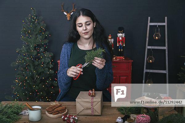 Junge Frau schneidet Zweig zum Dekorieren von Weihnachtsgeschenken