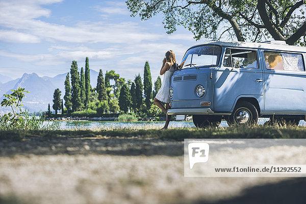 Italien  Gardasee  junge Frau beim Kaffeetrinken im Campingbus