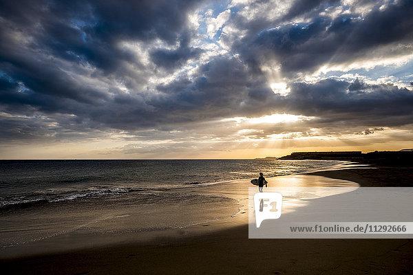 Spanien  Teneriffa  Junge mit Surfbrett am Strand bei Sonnenuntergang