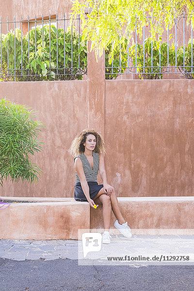 Ernsthafte junge Frau vor der Wand sitzend Ernsthafte junge Frau vor der Wand sitzend