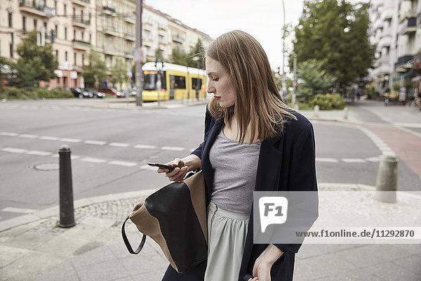 Frau in der Stadt beim Blick auf das Handy