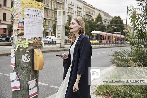 Frau in der Stadt mit Handy