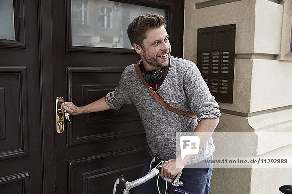Mann mit Fahrrad an der Haustür Mann mit Fahrrad an der Haustür