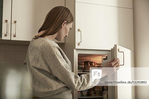 Frau schaut in den Kühlschrank