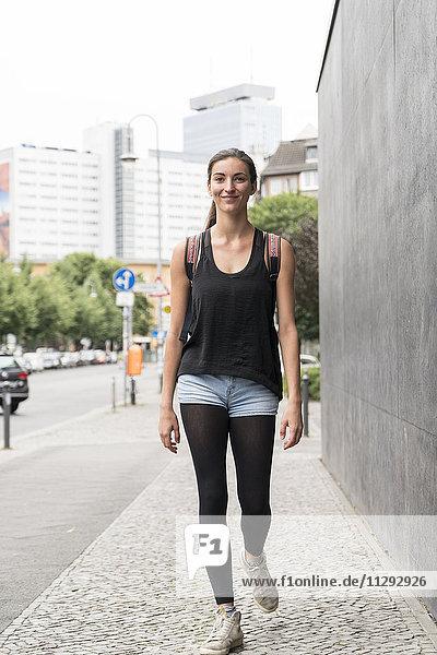 Lächelnde junge Frau auf dem Gehsteig