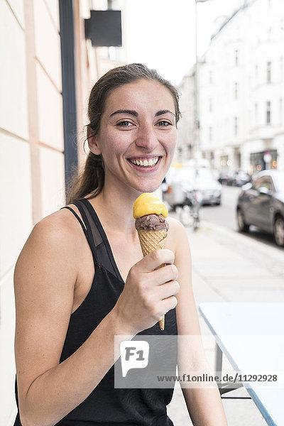 Porträt einer glücklichen jungen Frau mit Eistüte