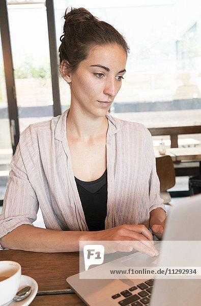 Junge Frau arbeitet mit Laptop in einem Coffee-Shop